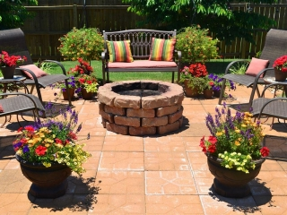 Patio with chairs and fireplace in the center